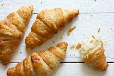 Fototapete Goldenen Croissants auf rustikalem Holz weiß, von oben.