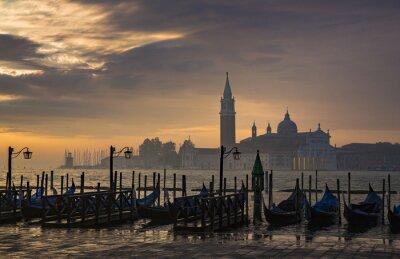 Fototapete Gondolas by Saint Mark square during sunrise with San Giorgio di Maggiore church in the background in Venice Italy