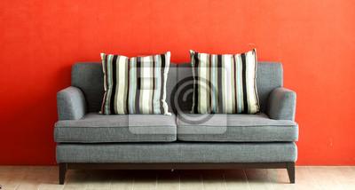 graues Sofa auf rotem Stuck Hintergrund setzen