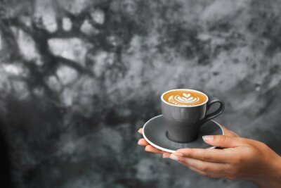 Fototapete Gray cup of fresh cappuccino in woman hands on background of gray concrete cement textured wall. Trendy hipster cafe design.