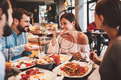 Fototapete Group of Happy friends having breakfast in the restaurant