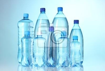 Gruppe Plastikflaschen mit Wasser auf blauem Hintergrund