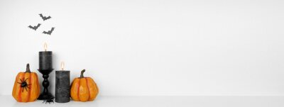 Fototapete Halloween shelf display with pumpkins, black candles and spiders against a white wall with bats. White shelf. Banner with copy space.