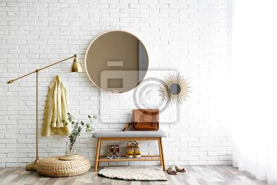 Fototapete Hallway interior with big round mirror and shoe storage bench near brick wall