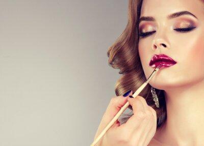 Fototapete Hand des Make-up-Master, Malerei Lippen der jungen schönen Modell. Makeup im Gange.