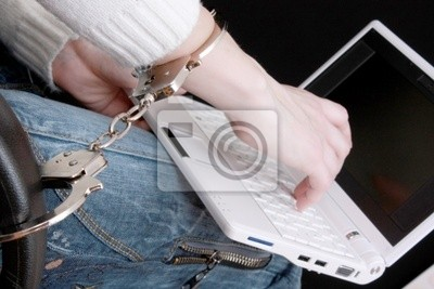 Hand in handcuffs on laptop
