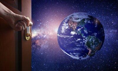 Fototapete Hand öffnet leere Raumtür zu Planetenerde vom Raum. Etwas