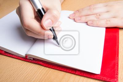 Hand schreiben in rotes Notizbuch