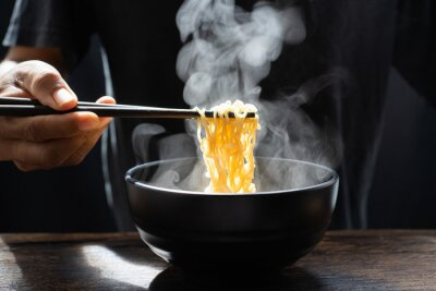 Fototapete Hand uses chopsticks to pickup tasty noodles with steam and smoke in bowl on wooden background, selective focus. Asian meal on a table, hot food and junk food concept