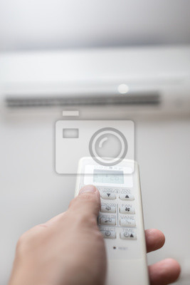 hand with remote control air conditioner blur background