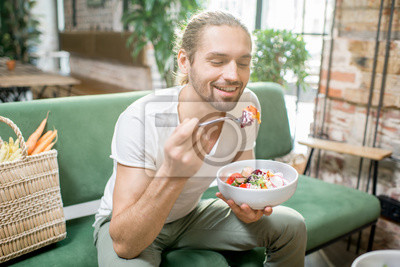 Fototapete Handsome man eating healthy salad sitting indoors on the green sofa with bag full of vegetables on the background. Healthy eating concept
