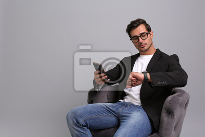 Fototapete Handsome young businessman with smartphone checking time while sitting in armchair on grey background. Space for text