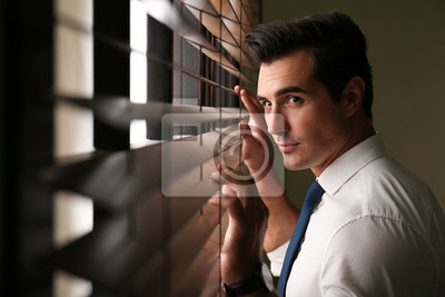 Fototapete Handsome young man looking through window blinds indoors