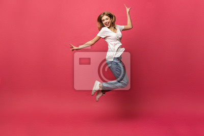 Fototapete happiness, freedom, motion and people concept - smiling young woman jumping in air over pink background