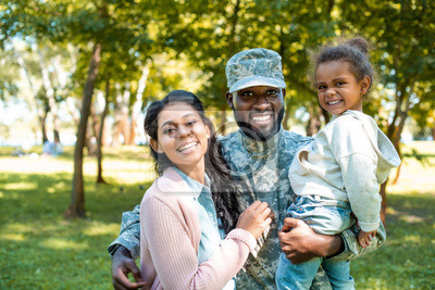 Fototapete happy african american soldier in military uniform looking at camera with family in park