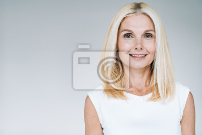 Fototapete happy blonde mature woman smiling isolated on grey