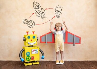Fototapete Happy child with cardboard wings. Funny kid playing with toy handmade robot. Success, creative and innovation technology concept