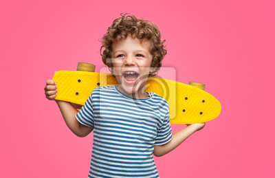 Fototapete Happy curly boy laughing and holding skateboard