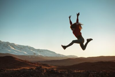 Fototapete Happy girl jumps against mountains at sunset