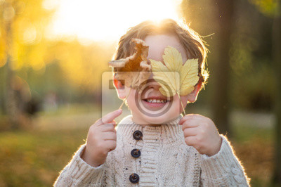 Fototapete Happy little child baby boy laughing and playing in the autumn