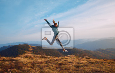 Fototapete Happy woman hiker jumping on mountain ridge on blue cloudy sky and mountains background. Travel and active lifestyle concept.