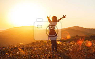 Fototapete Happy woman jumping and enjoying life  at sunset in mountains.