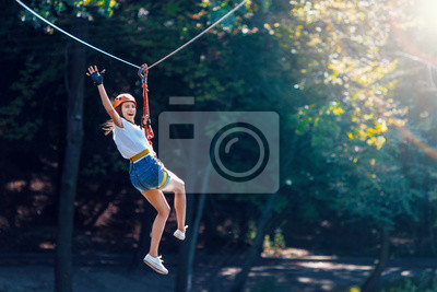 Fototapete Happy women girl female gliding climbing in extreme road trolley zipline in forest on carabiner safety link on tree to tree top rope adventure park. Family weekend children kids activities concept