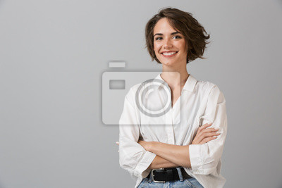 Fototapete Happy young business woman posing isolated over grey wall background.