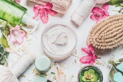 Fototapete Hautcreme mit Blumenblättern und anderen Körperpflegekosmetikprodukten und -zubehör auf weißem Hintergrund, Draufsicht