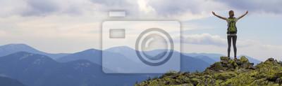 Fototapete Hintere Ansicht des jungen schlanken Rucksacktouristen-Touristenmädchens mit erhobenen Armen, die auf felsiger Spitze gegen hellblauen Morgenhimmel stehen und nebliges Gebirgspanorama genießen.  Touri
