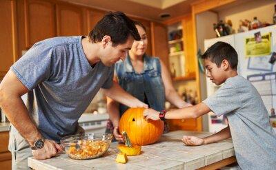 Fototapete hispanic american family carving pumpkin into jack o lantern at home
