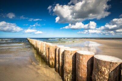 Fototapete Hölzerne Wellenbrecher am sandigen Strand von Leba am späten Nachmittag, Ostsee
