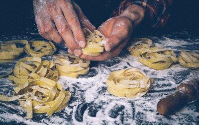 Fototapete Homemade uncooked pasta on black background. Making fresh italian fettuccine.