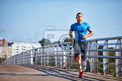 Fototapete Hübscher athletischer Mann, der heraus in der Stadt rüttelt