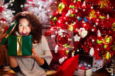hübsches Mädchen öffnet Geschenk vor dem Weihnachtsbaum
