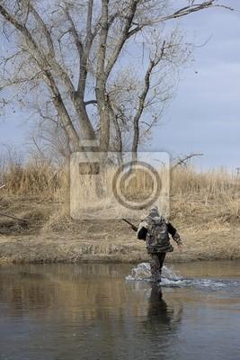 Hunter in Camouflage Tücher mit einem Gewehr einen Fluss überqueren