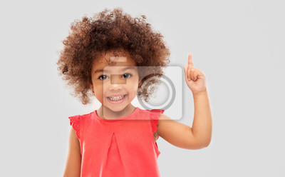 Fototapete idea, warning and childhood concept - happy little african american girl pointing finger up over grey background