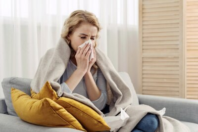 Fototapete Ill woman with runny nose sneezes into a napkin