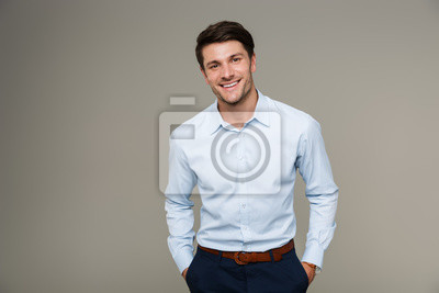 Fototapete Image of happy brunette man wearing formal clothes smiling at camera with hands in pockets