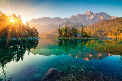 Fototapete Impressive summer sunrise on Eibsee lake with Zugspitze mountain range. Sunny outdoor scene in German Alps, Bavaria, Germany, Europe. Beauty of nature concept background.
