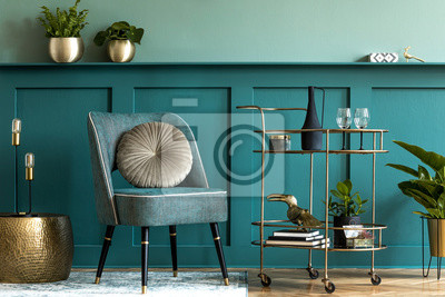 Fototapete Interior design of luxury living room with stylish armchair, gold liquor cabinet, a lot of plants and elegant personal accessories. Green wall panelling with shelf. Modern home decor. Template.