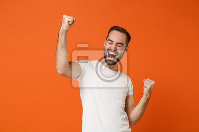 Fototapete Joyful young man in casual white t-shirt posing isolated on orange background in studio. People sincere emotions lifestyle concept. Mock up copy space. Clenching fists like winner keeping eyes closed.