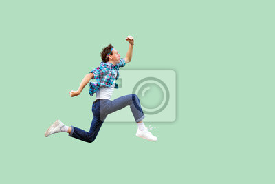 Fototapete Jump to the success. Full length profile side view of active young man in casual blue checkered shirt and headband running very fast or jumping. indoor studio shot, isolated on green background.