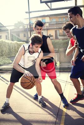 Junge Basketballspieler spielen mit Energie
