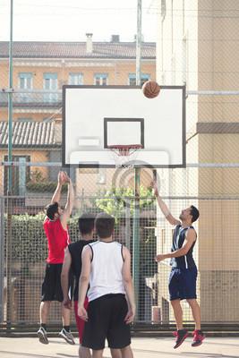 Junge Basketballspieler spielen mit Energie in einem städtischen Ort
