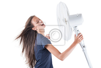 Junge Frau, die sich abkühlt unter Wind der Lüfter