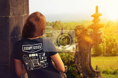 Junge Frau in einem Tempel mit dem Blick über Bali als Backpacker Tourist