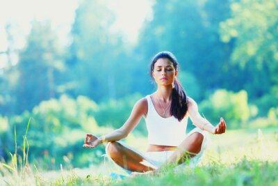 Fototapete Junge Frau macht Yoga-Übung im grünen Park