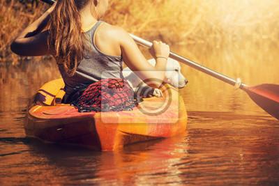 Junge Frau mit jungem Hund in einem Kanu auf einem Fluss bei Sonnenuntergang