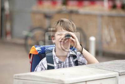 Junge mit schulranzen schaut durch ein fernrohr fototapete